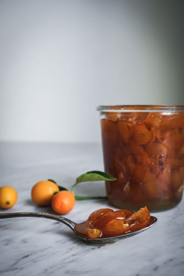 A spoon resting on counter filled with candied kumquats