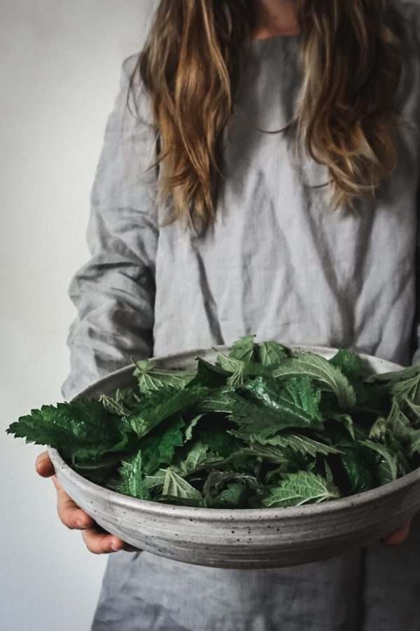 Woman in grey dress holds a bowl of stinging nettles