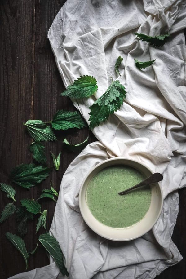 bowl of green nettle soup on table decorated with cloth and loose nettle leaves
