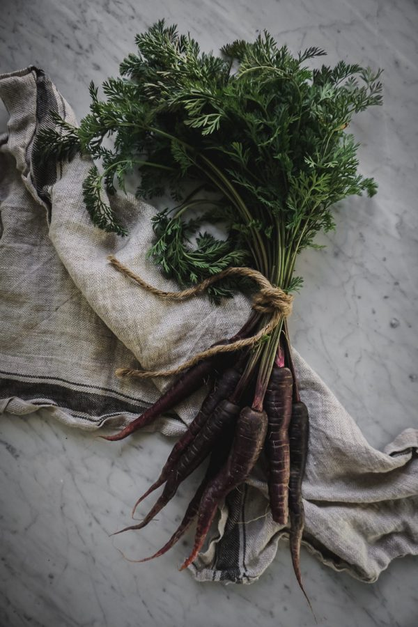 a bundle of purple carrots tied with a string