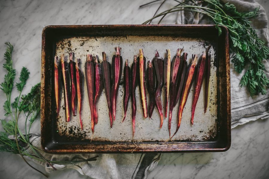 colorful carrots sliced in half arranged on a baking pan