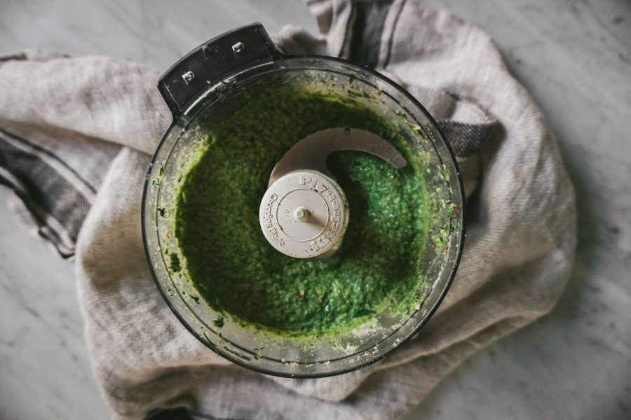 looking into a food processor filled with green pesto